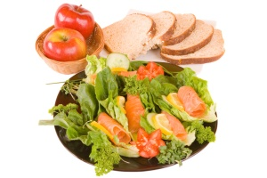 Salad topped with Salmon, apples and bread slices